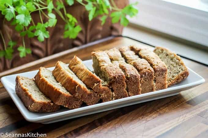 Super moist and delicious banana bread sliced and ready to eat placed on a white rectangular place on a beautiful walnut board.