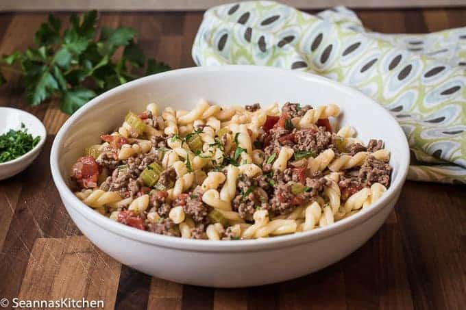Oma's Spaghetti - Gremelli Pasta with sauce made with ground beef, onions, celery, fresh tomatoes and butter, served in a wide white bowl that is placed on a walnut cutting board, napkin placed nearby, with a little fresh green parsley