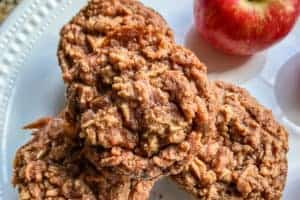 Apple Cinnamon Oatmeal Muffins stacked with Red Apple in right corner of image