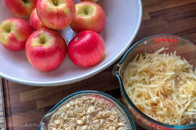 Fresh red Honeycrisp apples in a white bowl in the upper left corner, oats soaking in water and grated apples also shown in measuring cups