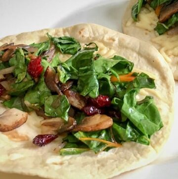 Beautiful Green Leafy Chopped Swiss Chard and Mushroom Wraps on 2 Flour Tortillas served on a white plate.
