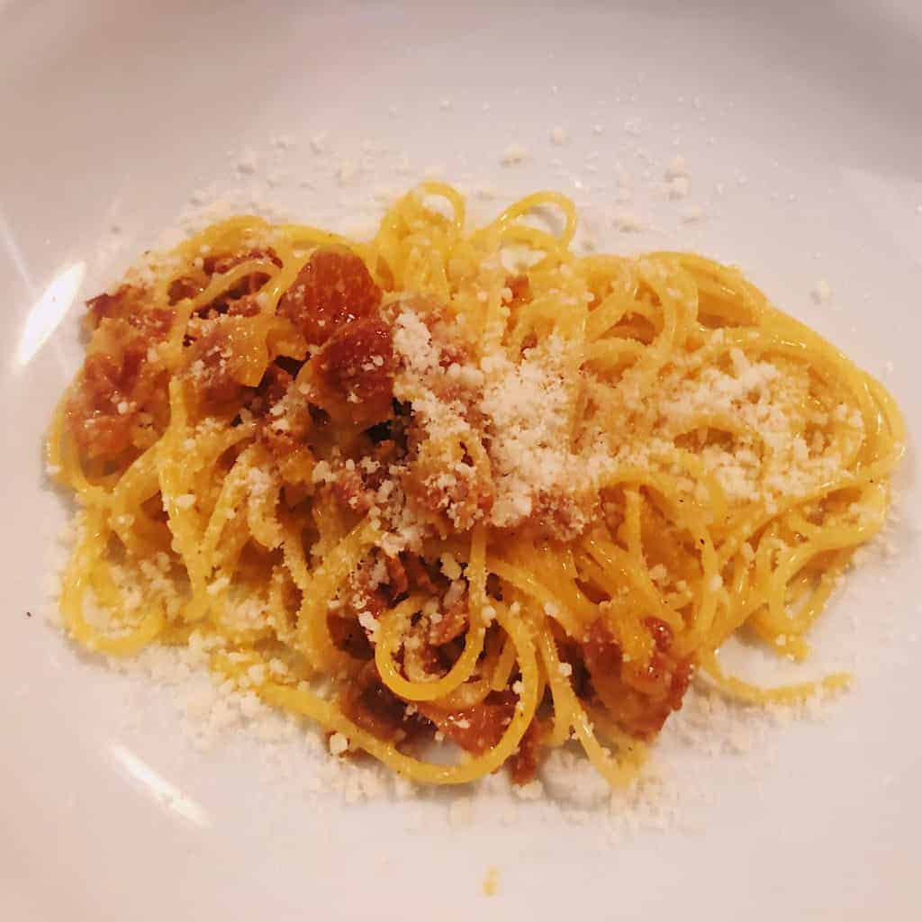 Pasta Carbonara topped with Parmigiano-Reggiano on a white plate