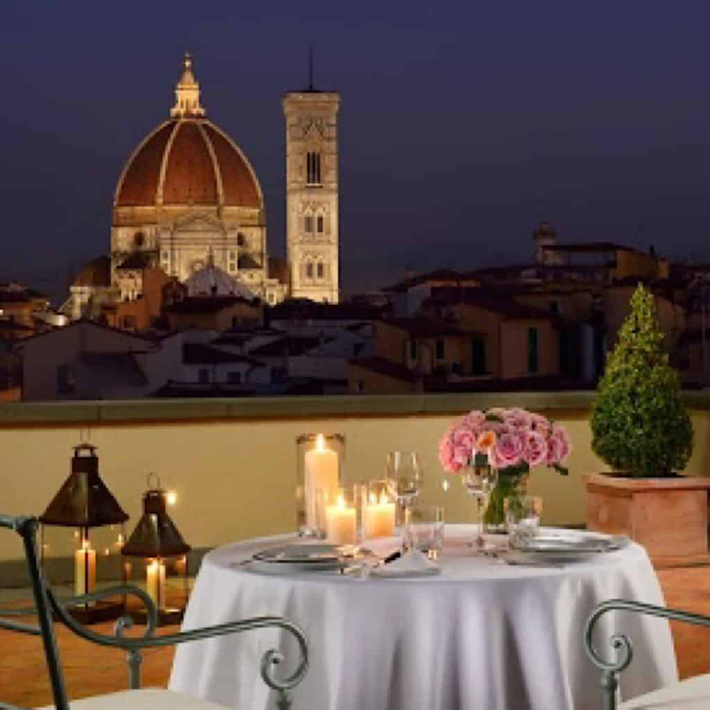 Evening balcony setting with white table cloth and candles overlooking Duomo