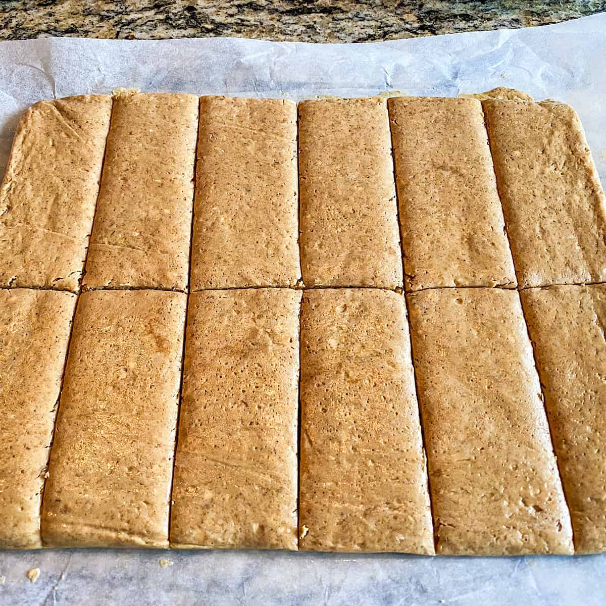 Dough divided into 12 bars placed on parchment paper