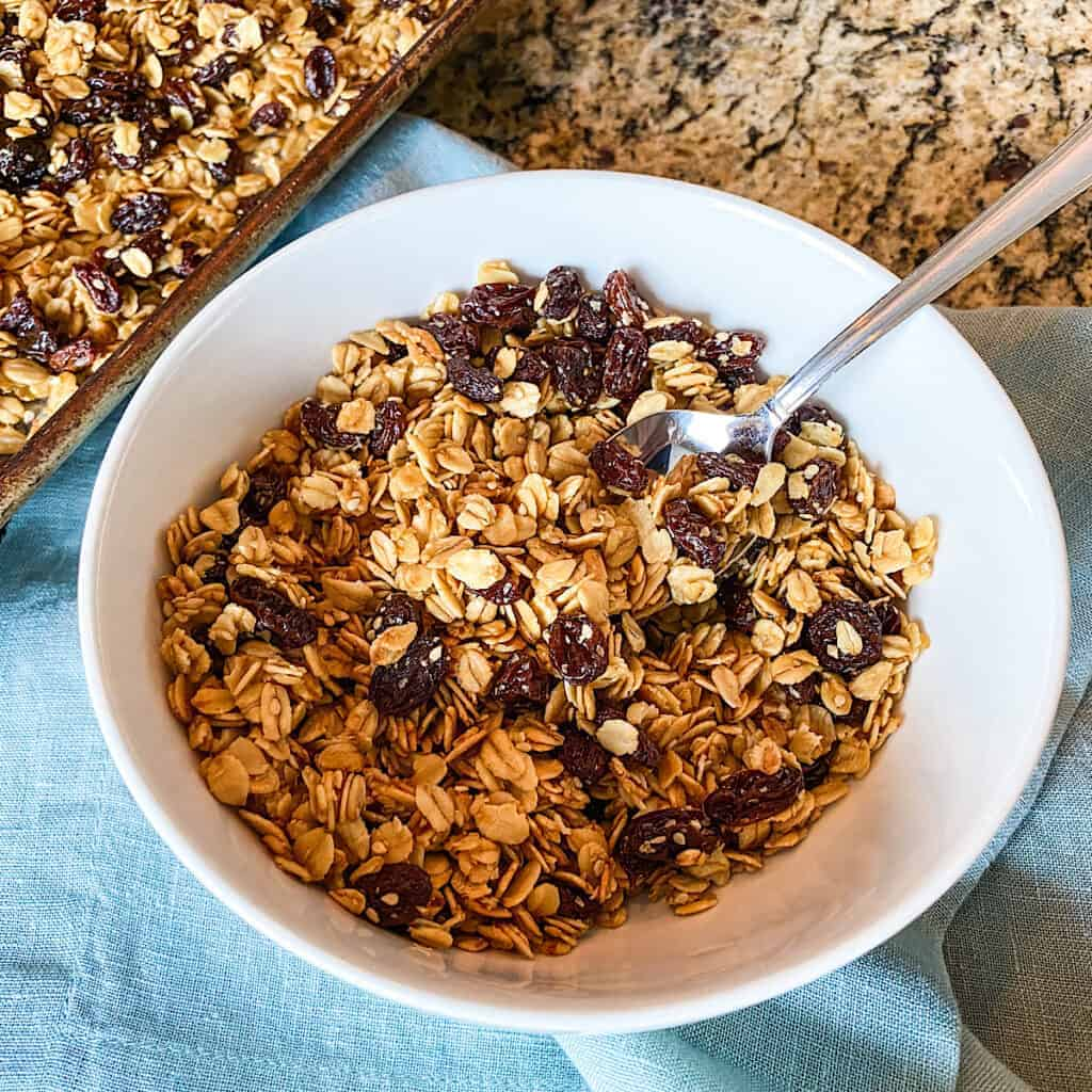 Fresh and delicious homemade granola made with oats, raisins, and honey pictured in a white bowl with spoon placed on blue napkin
