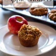 One fresh apple muffin placed on a white plate with an apple. Muffin tin filled with muffins is visible in background.