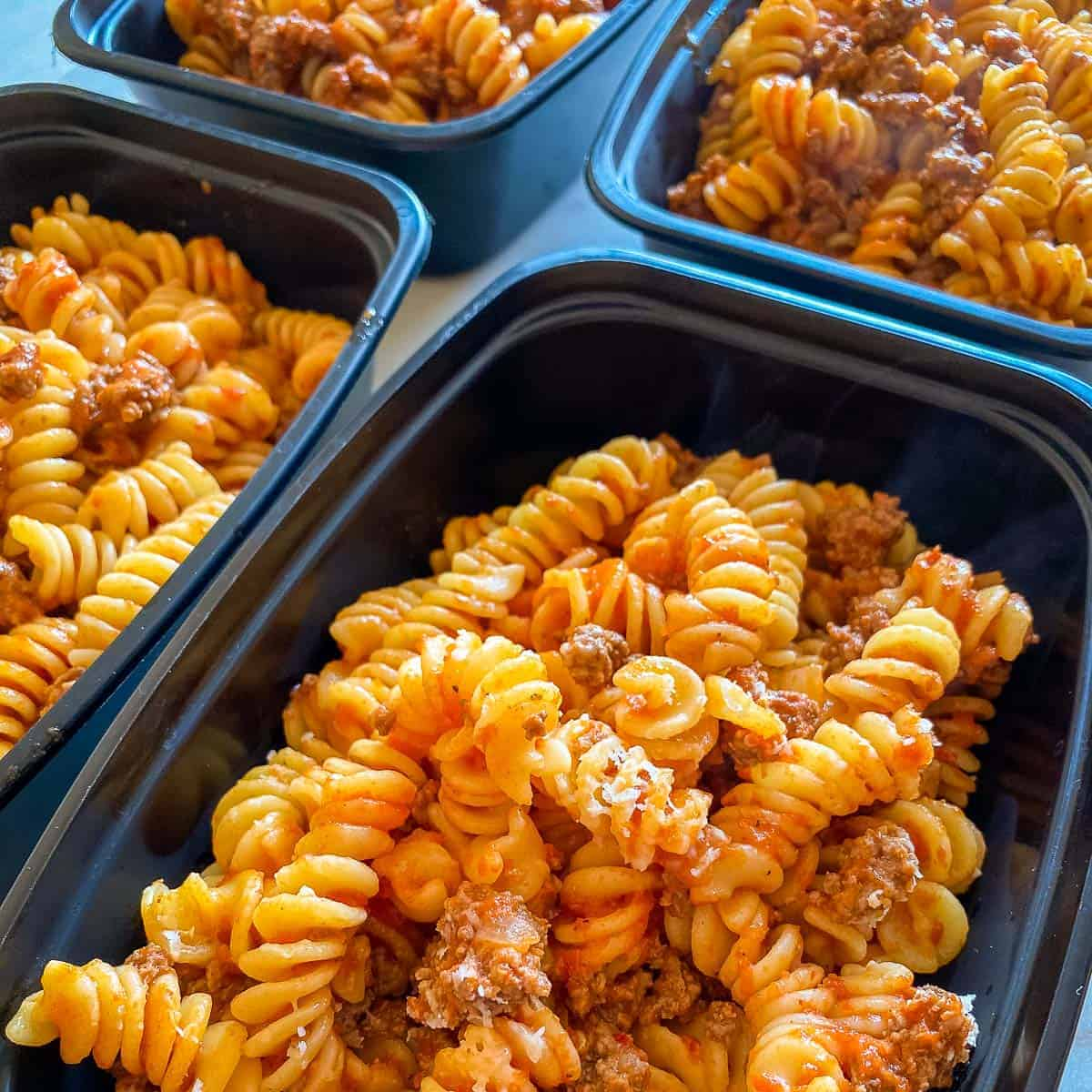 4 partial containers of Bison Pasta made with rotini divided into 4 rectangular black meal prep containers.