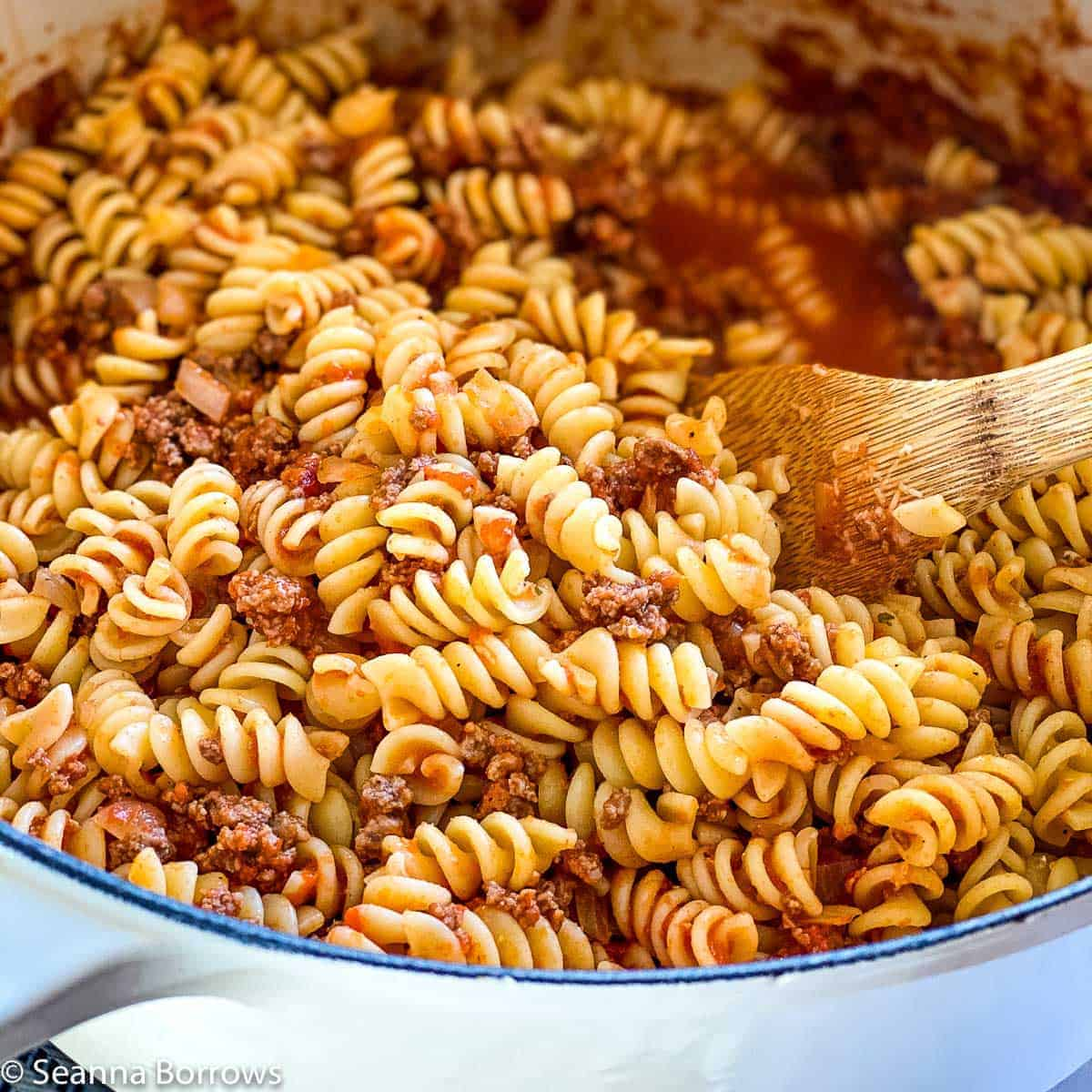 Ground Bison Pasta made with rotini pictured in off white Le Creuset dutch oven with wooden spoon gently lifting up some of the pasta.