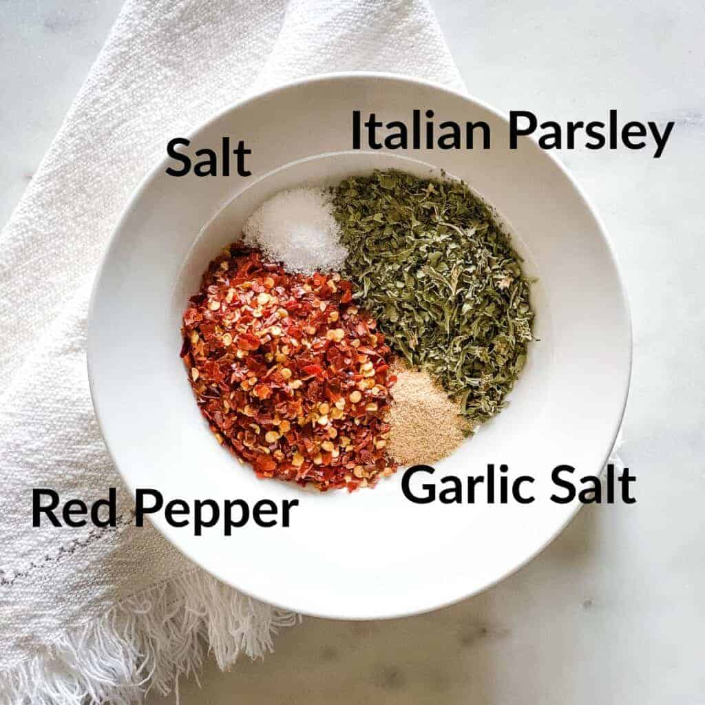 White bowl with spices arranged in a circle and labeled clockwise from top: Italian Parsley, Garlic Salt, Red Pepper, and Salt. Bowl is placed on a off white, fringed napkin on a white marble background.