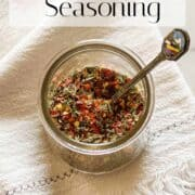 Red and green Italian Seasoning mixture pictured in a clear glass straight sided cup with little antique spoon. Pictured on a cream colored fringed napkin.