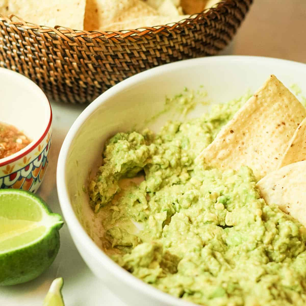 Image of The Best Guacamole shown with a basket of fresh chips on the left and some salsa.
