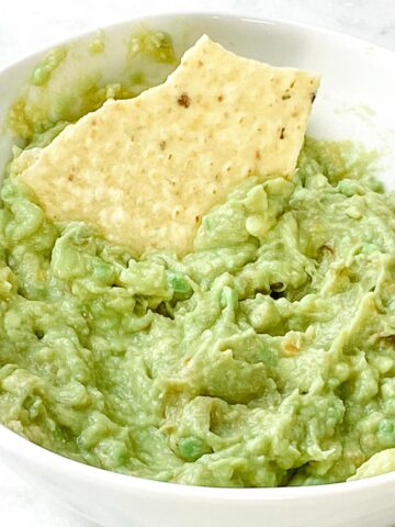 Guacamole with a chip inside a white bowl