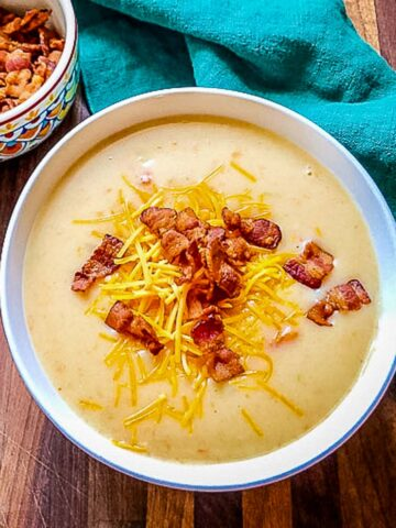 A white bowl of delicious Cheesy Potato Soup sprinkled with salty bacon bits and cheddar cheese. Little bowl of bacon bits sits next to soup on an evergreen colored linen napkin.