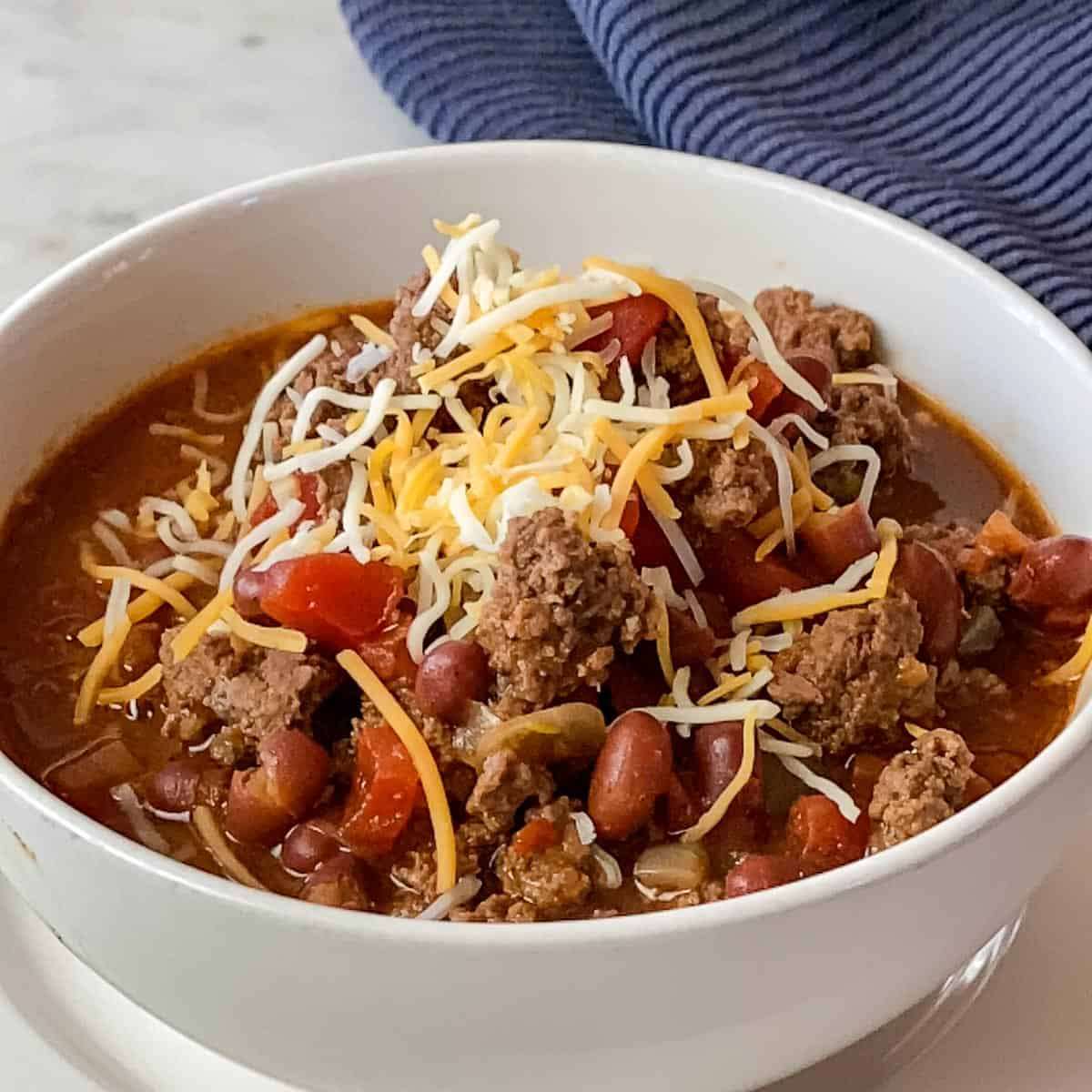 Bowl of Ground Bison Chili Recipe with a navy colored napkin in upper right corner.