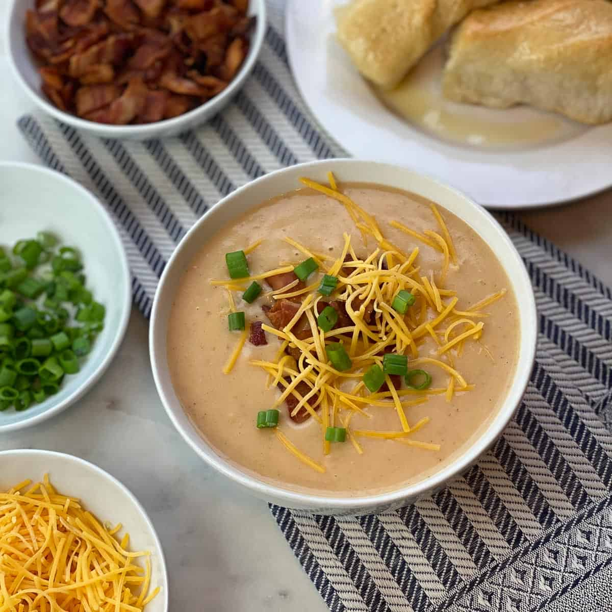 Image showing Potato Soup with toppings of bacon bits, Cheddar cheese, and green onions.