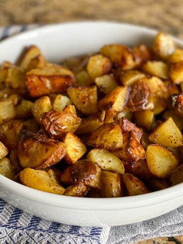 Crispy Oven Roasted Potatoes piled in a white bowl on a striped kitchen towel.