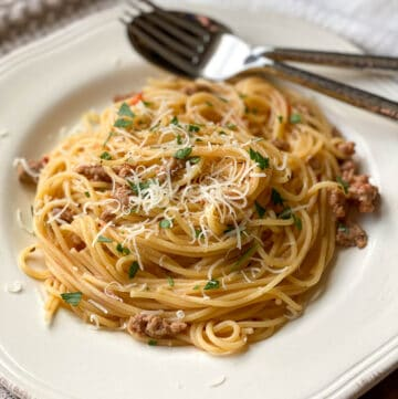 Image of Ground Turkey Pasta with grated parmesan cheese on white plate with fork and spoon.