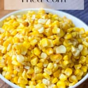 Fried Corn in a white bowl on cutting board with blue kitchen towel in upper right hand corner.