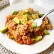 White plate full of Instant Pot Mexican Casserole with topped with fresh avocado.