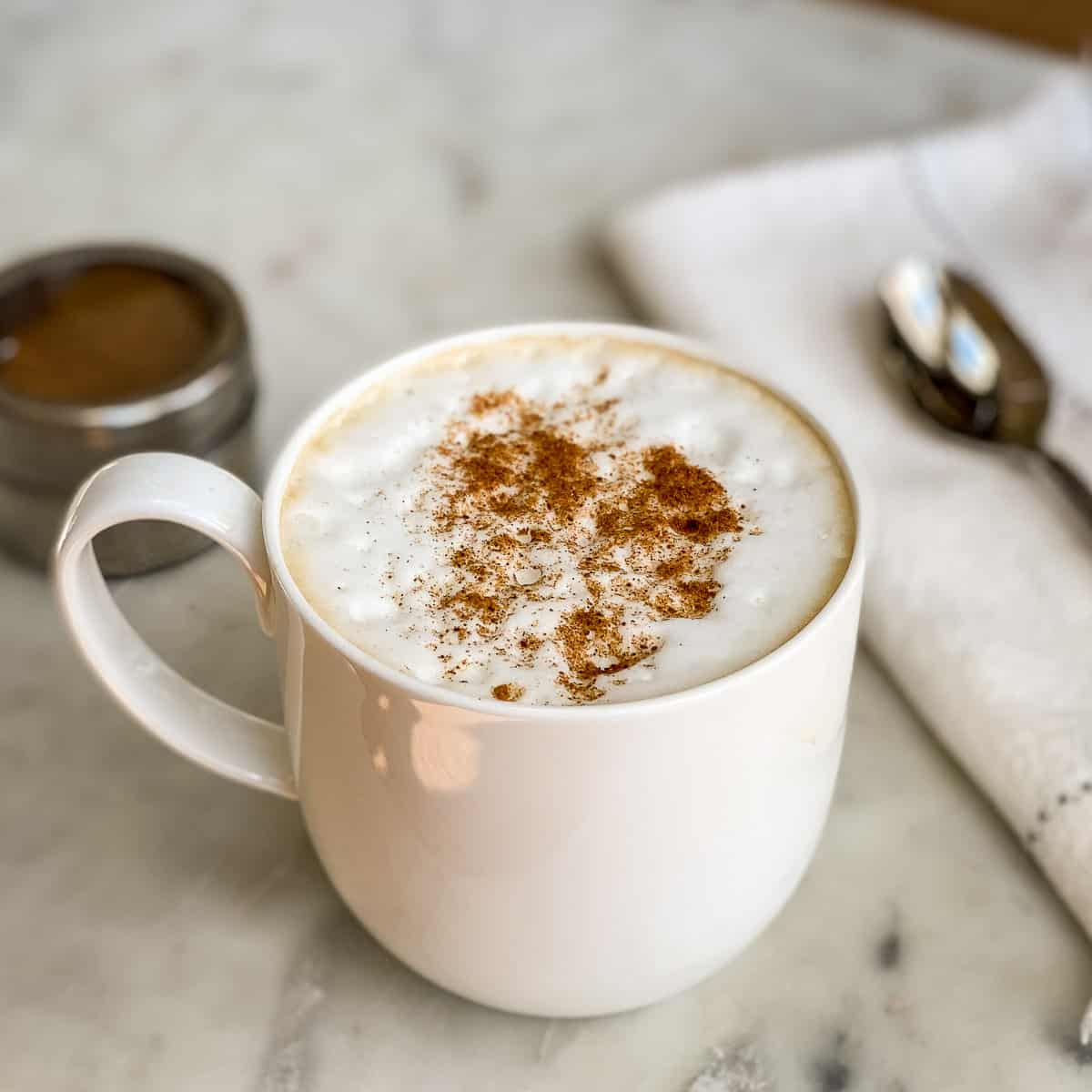 White coffee cup with Pumpkin Spice sprinkled on a Pumpkin Spice Latte with spoon and spices in background.