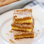 Three Pumpkin Squares stacked on white plate with pan in background.